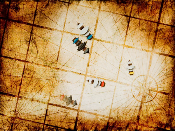 Digital still of the virtual battlefield seen through the tangible lens. Allied ships (white sails) are always visible and opponent ships (black sails) are only visible when in range. The shroud of the fog hides one of the enemy ships.